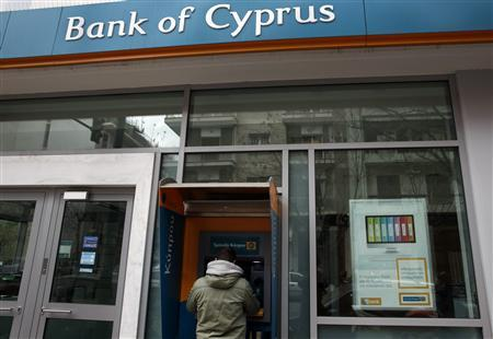 A man withdraws money from an automatic teller machine at a branch of Bank of Cyprus, in Athens March 16, 2013. REUTERS/Yannis Behrakis