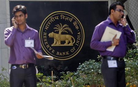 Two men make phone calls while standing near a Reserve Bank of India (RBI) crest at the RBI headquarters in Mumbai January 29, 2013. REUTERS/Vivek Prakash/Files