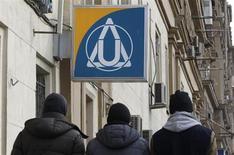 Люди проходят мимо отделения Юниаструм банка в Москве, 18 марта 2013 года. Российские банки, которые держат около $12 миллиардов на счетах в кипрских банках, и которым компании из этого офшора должны до $40 миллиардов, поспешили откреститься от рисков из-за введения налога на депозиты ради финансовой помощи Кипру со стороны ЕС, отказавшись раскрыть объемы бизнеса с островом. REUTERS/Sergei Karpukhin