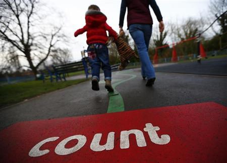 A woman walks a child on to a playground in Loughborough, central England January 29, 2013. REUTERS/Darren Staples