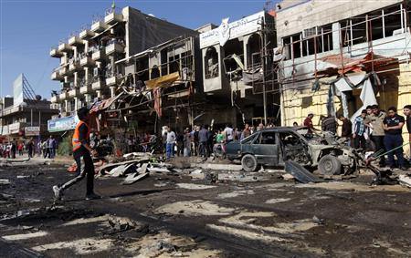 Residents gather at the site of a car bomb attack in the AL-Mashtal district in Baghdad March 19, 2013. A series of coordinated car bombs and blasts hit Shi'ite districts across Baghdad and south of the Iraqi capital on Tuesday, killing at least 25 people on the tenth anniversary of the U.S.-led invasion. REUTERS/Mohammed Ameen