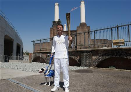 Former England striker Michael Owen carries the Olympic Torch through Battersea dogs home with a Staffordshire Bull Terrier called Rory in London July 23, 2012. REUTERS/Ki Price