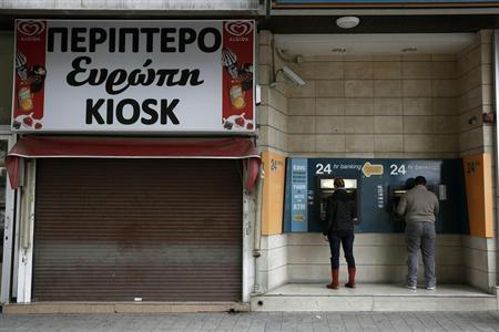 Bank customers make transactions at an automated teller machine (ATM) outside a closed branch of the Bank of Cyprus in Nicosia March 19, 2013. REUTERS/Yorgos Karahalis