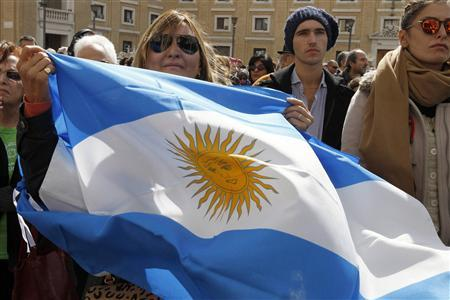 A woman waves an Argentinian flag while Pope Francis celebrates his inaugural mass in Saint Peter Square at the Vatican March 19, 2013. REUTERS/Giampiero Sposito