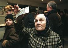 Пожилая женщина изучает новую 10-рублевую банкноту в отделении Сбербанка России 5 января 1998 года. Рубль стабилен во вторник перед голосованием на Кипре и заседанием ФРС. REUTERS/Sergei Karpukhin