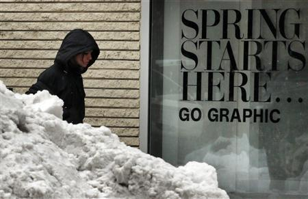 A pedestrian walks past a pile of snow, and the words ''Spring Starts Here'' in a store window, during a late winter snow storm in Boston, Massachusetts March 19, 2013. REUTERS/Brian Snyder