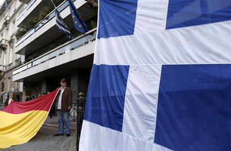 Protesters hold a Spanish flag next to a Greek flag during a rally against a levy on bank deposits in Cyprus, outside of the European Union office in Athens March 19, 2013. REUTERS/John Kolesidis