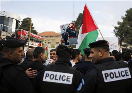 Palestinian policemen stand in front of demonstrators holding digitally manipulated placards depicting U.S President Barack Obama, to prevent them from reaching the main offices of Palestinian President Mahmoud Abbas, during a protest in the West Bank city of Ramallah March 19, 2013. REUTERS/Ammar Awad