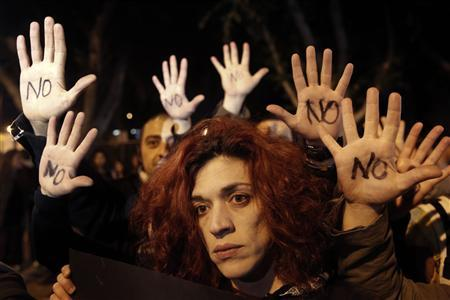 Anti-bailout protesters raise their open palms showing the word 'No' after Cyprus's parliament rejected a proposed levy on bank deposits in Nicosia March 19, 2013. REUTERS-Yorgos Karahalis