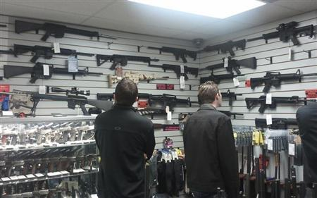 Customers view semi automatic guns on display at a gun shop in Los Angeles, California December 19, 2012. REUTERS/Gene Blevins