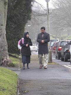 Malala Yousufzai walks with her father Ziauddin as she attends Edgbaston High School for girls in Edgbaston, central England in this handout photograph released March 19, 2013. REUTERS/Edelman/Handout