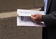 A man walks away from the St. Regis hotel reading information regarding investing in the upcoming IPO of Facebook in New York May 10, 2012. REUTERS/Lucas Jackson