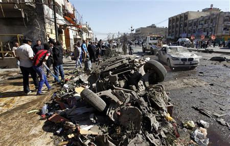 Residents gather at the site of a car bomb attack in the AL-Mashtal district in Baghdad March 19, 2013. REUTERS/Mohammed Ameen