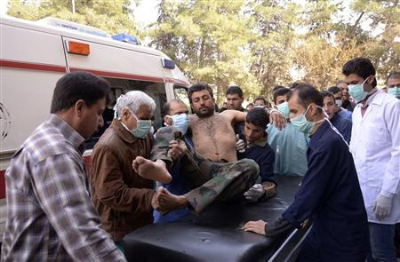Residents and medics transport a Syrian Army soldier, wounded in what they said was a chemical weapon attack near Aleppo, to a hospital March 19, 2013. REUTERS/George Ourfalian