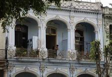 A woman looks from the balcony of her apartment in a colonial-style house in Havana March 18, 2013. REUTERS/Desmond Boylan