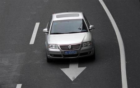 A Volkswagen Passat drives along a busy street in downtown Shanghai March 20, 2013. REUTERS/Carlos Barria