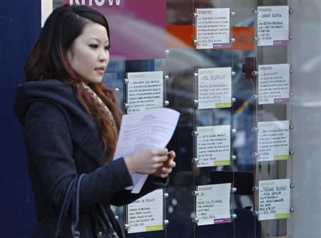 A woman leaves a recruitment centre in London December 14, 2011. REUTERS/Luke MacGregor