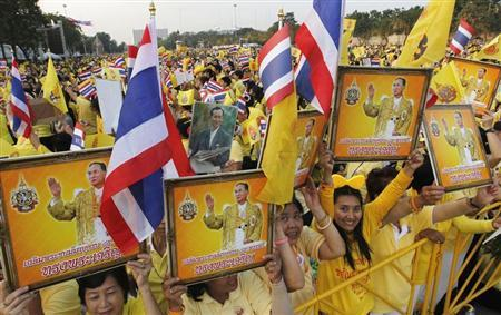 People hold pictures of Thailand's King Bhumibol Adulyadej as they wait for him to arrive at the Anantasamakom Throne Hall in Bangkok December 5, 2012. REUTERS/Sukree Sukplang