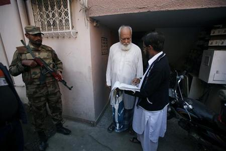 A Pakistan Army soldier (L) stands guard while an election commission worker (R) verifies a voter in a residential area of Karachi January 29, 2013. REUTERS/Athar Hussain