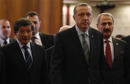 Turkey's Prime Minister Recep Tayyip Erdogan arrives for a news conference as he is flanked by Foreign Minister Ahmet Davutoglu (L), Economy Minister Zafer Caglayan (R) and officials before his flight to Denmark for an official visit at Esenboga Airport in Ankara March 19, 2013. REUTERS/Umit Bektas