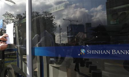A man uses his mobile phone at Shinhan Bank automated teller machines (ATM) as employees (L) of the bank put a 'out of service' notice for the ATMs, on a window after a hacking attack in central Seoul March 20, 2013. REUTERS-Lee Jae-Won