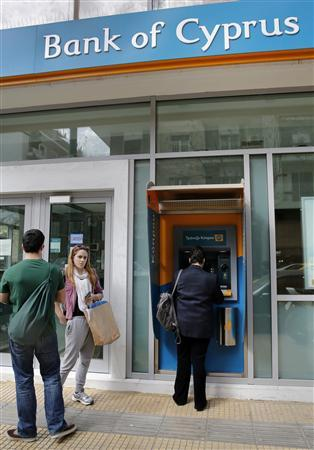 People line up to make transactions at an ATM machine outside a Bank of Cyprus branch in Athens March 20, 2013. REUTERS/Yannis Behrakis