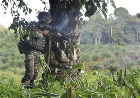 A Malaysian soldier uses a weapon in the area of Sungai Nyamuk, a village adjacent to Kampung Tanduo where troops stormed the camp of an armed Filipino group, in Lahad Datu, Sabah state, March 12, 2013 in this picture provided by Malaysia's Ministry of Defence. REUTERS/Malaysia's Ministry of Defence/Handout