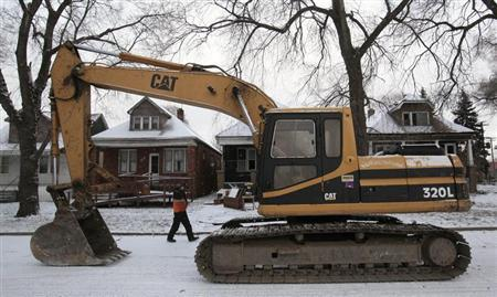 A Caterpillar excavator sits on a neighborhood street as the Hantz Woodlands work crew readies to demolish two vacant and blighted houses frequented by squatters and drug users in a once thriving eastside neighborhood of Detroit, Michigan January 25, 2013. REUTERS/Rebecca Cook