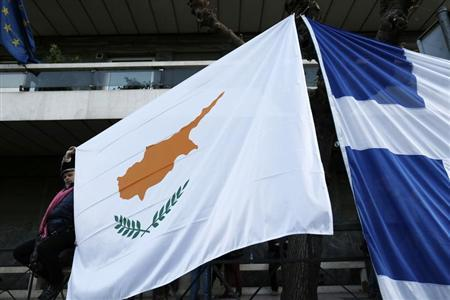 A protester holds a Cypriot flag next to a Greek flag during a rally against a levy on bank deposits in Cyprus, outside of the European Union office in Athens March 19, 2013. REUTERS/John Kolesidis
