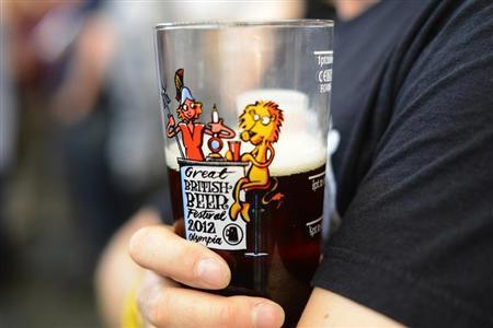 A man holds a glass of beer at the Great British Beer Festival at Olympia, London August 8, 2012. REUTERS/Paul Hackett