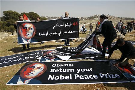 Palestinian activists organise banners depicting U.S. President Barack Obama at a protest camp in an area known as ''E1'', which connects the two parts of the Israeli-occupied West Bank outside Arab suburbs of East Jerusalem March 20, 2013. Palestinian activists set up the protest camp on Wednesday close to where Israel wants to build a new settlement, drawing attention to their struggle for land during a visit to the region by Obama. REUTERS/Ammar Awad