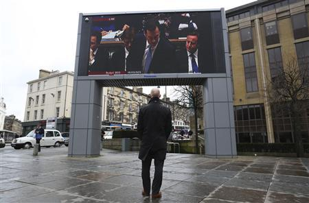 A man watches a screen showing Britain's Chancellor of the Exchequer George Osborne delivering his budget, Edinburgh in Scotland March 20, 2013. REUTERS/David Moir