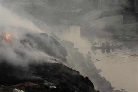 People cross the polluted Buriganga river by boat as smoke emits from a dump yard during sunset in Dhaka January 19, 2013. REUTERS/Andrew Biraj