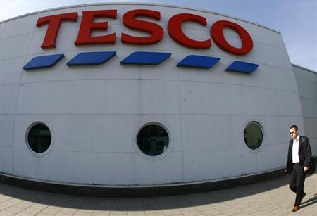 A pedestrian passes a Tesco store in central London June 9, 2008. REUTERS/Luke MacGregor