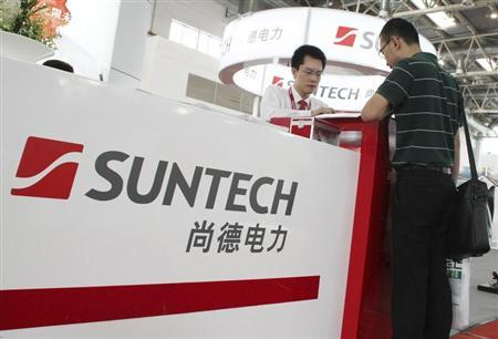 An employee (L) talks to a visitor at the Suntech booth of a photovoltaic industry exhibition in Beijing, September 5, 2012. REUTERS/Stringer
