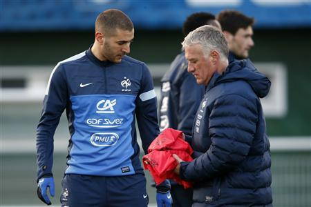 France's national team coach Didier Deschamps (R) passes by Karim Benzema (L) during a training session in Clairefontaine, near Paris, March 20, 2013. REUTERS/Charles Platiau