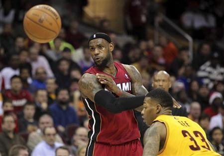 Miami Heat's LeBron James (L) passes the ball past Cleveland Cavaliers defender Alonzo Gee (33) during the third quarter of their NBA basketball game in Cleveland March 20, 2013. REUTERS/Aaron Josefczyk
