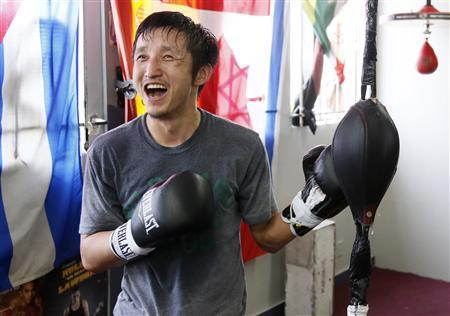 Two-time Olympic gold medalist and three-time world amateur boxing champion Zou Shiming of China laughs as he works out at the Wild Card Boxing Club while preparing for his upcoming professional boxing debut, in Los Angeles, March 20, 2013. REUTERS/Danny Moloshok