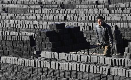 A worker pushes a cart at a coal factory in Shenyang, Liaoning province, March 5, 2013. REUTERS/Stringer