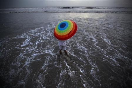 A man takes cover from rain under an umbrella along the shores of the Arabian Sea in Mumbai June 9, 2011. REUTERS/Danish Siddiqui