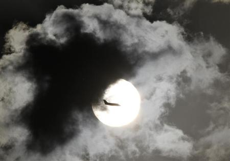 A passenger aircraft is silhouetted against the rising sun after taking off from New Delhi's Indira Gandhi International Airport April 3, 2012. REUTERS/B Mathur/Files