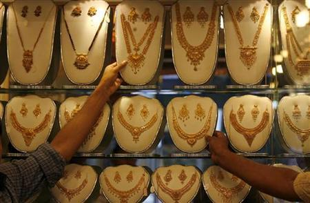 Shop keepers show gold jewellery to a customer inside their shop in Dhaka September 8, 2009. REUTERS/Andrew Biraj/Files