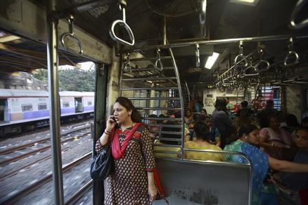 A woman speaks on the phone as she stands near the open doorway of a Ladies' Special train while travelling in Mumbai December 6, 2012. REUTERS/Navesh Chitrakar/Files