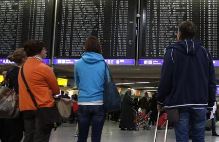 People look at a departure board during a five-hour warning strike by employees of German air carrier Lufthansa, following a pay dispute, represented by German united services union Ver.di at the Fraport airport in Frankfurt March 21, 2013. REUTERS/Lisi Niesner