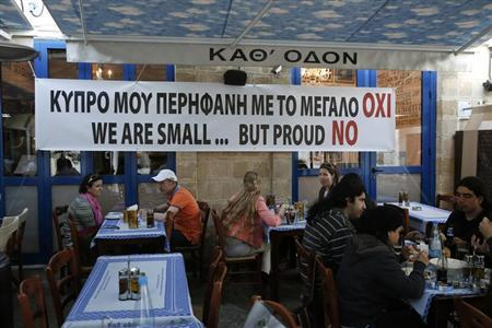 People eat at a restaurant under a banner placed by the owner in central Nicosia March 20, 2013. REUTERS/Yorgos Karahalis