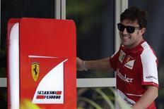 Piloto da Ferrari Fernando Alonso sorri ao entrar na suite de recepção da equipe no circuito internacional de Sepang, antes do Grande Prêmio da Malásia. 21/03/2013 REUTERS/Tim Chong