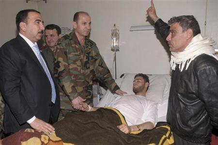 Syrian government officials and military personnel visit a victim of chemical weapons at a hospital in Aleppo, March 21, 2013. REUTERS/George Ourfalian
