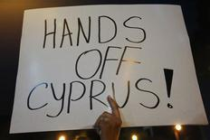 A protester holds a placard during a rally by employees of Cyprus Popular Bank outside the parliament in Nicosia March 21, 2013. REUTERS/Yannis Behrakis