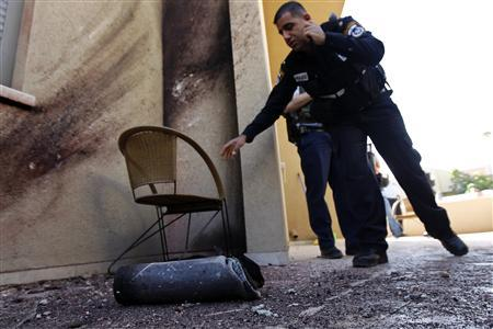 Israeli police officers stand near the remains of a rocket fired by Palestinian militants in Gaza after it landed in the southern Israeli town of Sderot March 21, 2013. REUTERS/Amir Cohen