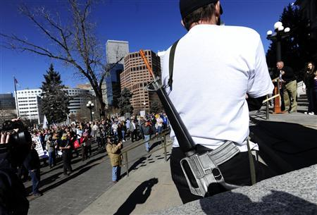 A man calling himself John Q. Citizen, a law abiding American, wears a toy assault rifle slung over his shoulder during the Guns Across America pro-gun rally at the State Capitol in Denver, Colorado, January 19, 2013. REUTERS/Mark Leffingwell